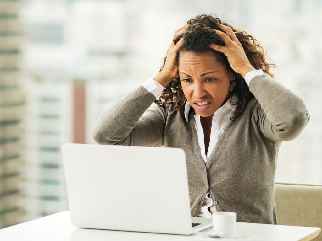 Broadband connection issues, business woman holding her head in disbelief